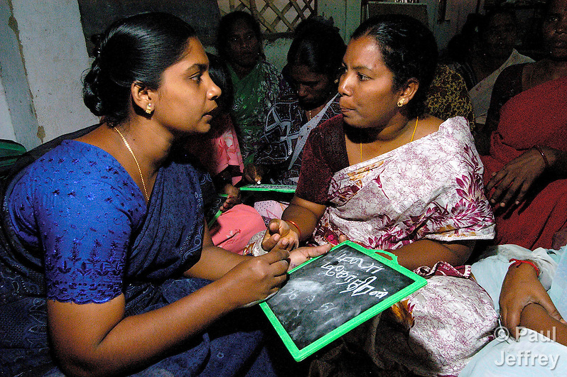 Carlione (left), a Methodist Bible Woman in the village of Bharathiyar Nagar, in the southern Indian state of Tamil Nadu, teaches basic literacy skills to other women in her village. (Paul Jeffrey)