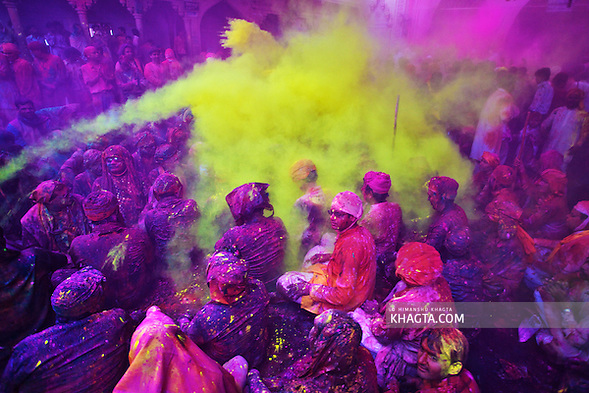 People covered with a layer of Purple colored powder gets sprayed with another layer of yellow while celebrating Braj Holi at Barsana village of Mathura. (Himanshu Khagta)