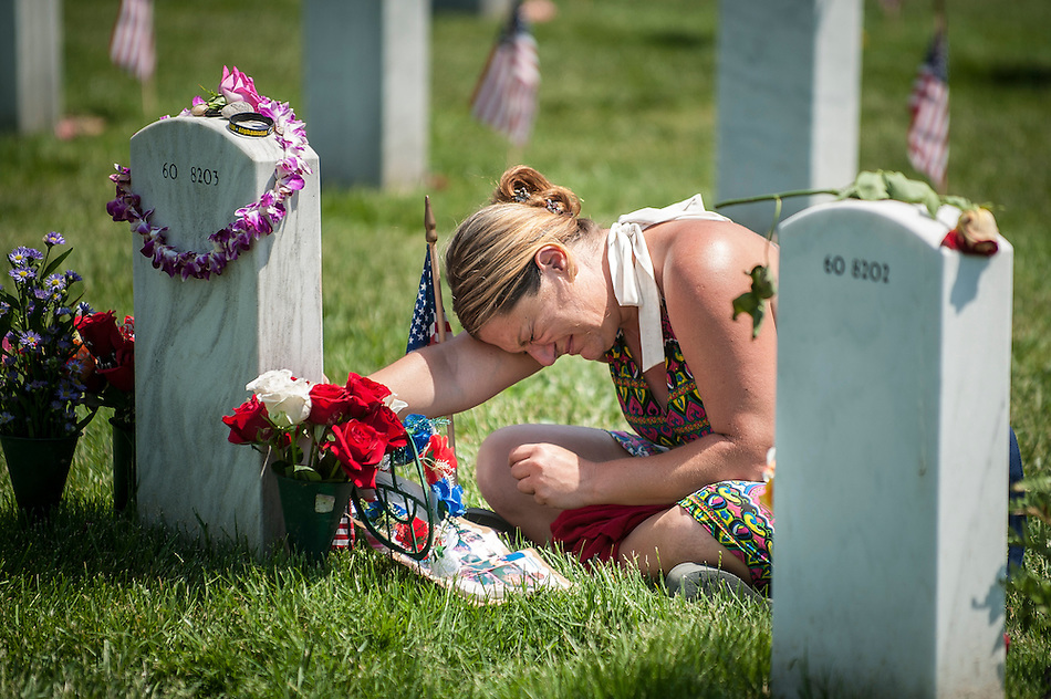Lauura Youngblood weeps over the grave of her husband Travis L. Youngblood at section 60 in Arlington National Cemetery on Memorial Day at Arlington National Cemetery in Arlington, Virginia, USA, on 26 May 2014. Laura Youngblood is also a veteran of the United States Navy. Her husband was killed during the Iraq War. (PETE MAROVICH/EPA)