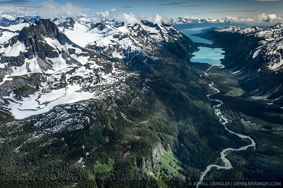 Connelly Lake (left) is a 90-acre alpine lake near Haines, Alaska that drains into the Chilkoot River (right). Connelly Lake (formerly known as Upper Chilkoot Lake) is the focus of a proposed $32 million, 12-megawatt hydroelectric project by Alaska Power and Telephone Company (AP&T). AP&T proposes to build a dam at the outlet of Connelly Lake that would create a 160-acre reservoir and a 6,200-foot-long penstock down the side of the mountain where water would be delivered to two turbine generators located in a powerhouse near the Chilkoot River into which the lake water would be discharged. Some of the main features of the proposed Connelly Lake project (for example portions of the penstock, the powerhouse, access roads, and the transmission line) would be located in the Alaska Chilkat Bald Eagle Preserve and the Haines State Forest. Environmental concerns include the impact construction and project operation would have on fish spawning and rearing habitat (water turbidity issues), and bald eagles. The eagles rely on the salmon that use the Chilkoot Valley in the fall and early winter when they are attracted to late spawning salmon runs. AP&T wants to build the project to replace the undersea cable that supplies Haines with electricity from Skagway. This photo of the ice and snow covered Connelly Lake was taken in mid-July. The large lake in the background is Chilkoot Lake. Beyond Chilkoot Lake is Lutak Inlet of the Lynn Canal. (John L. Dengler)