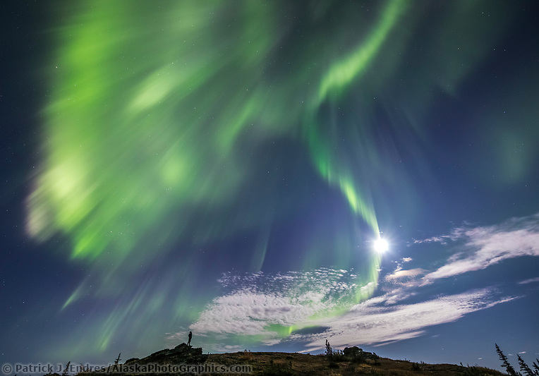 A man watches the aurora borealis, also called the northern lights, swirl over the foothills surrounding Fairbanks, Alaska. (Patrick J Endres / AlaskaPhotoGraphics.com)