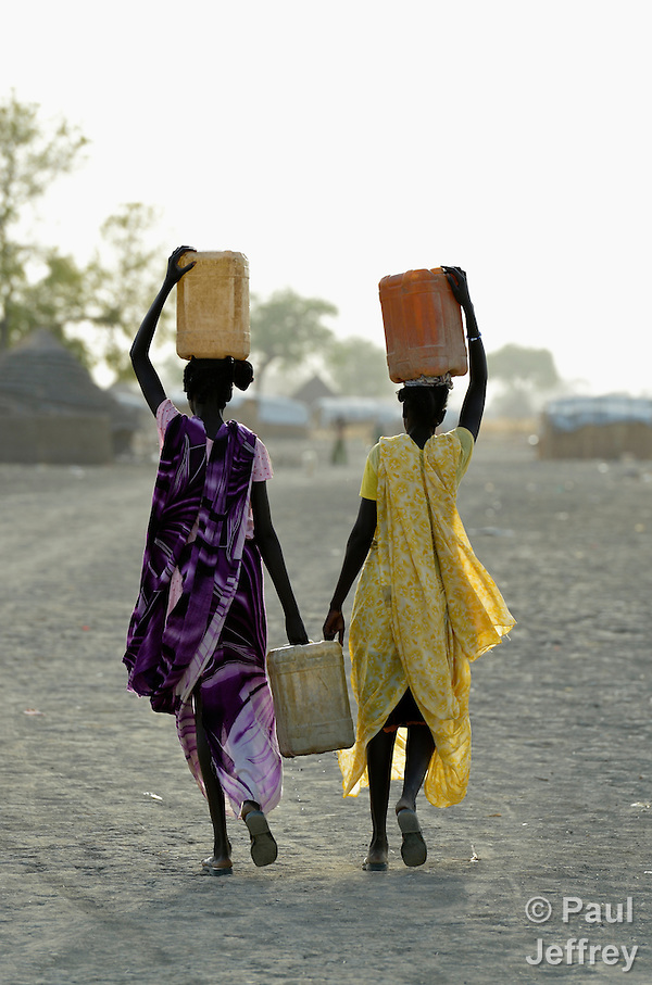 Women carry home water in Agok, a town in the contested Abyei region where tens of thousands of people fled in 2011 after an attack by soldiers and militias from the northern Republic of Sudan on most parts of Abyei. Although the 2005 Comprehensive Peace Agreement called for residents of Abyei--which sits on the border between Sudan and South Sudan--to hold a referendum on whether they wanted to align with the north or the newly independent South Sudan, the government in Khartoum and northern-backed Misseriya nomads, excluded from voting as they only live part of the year in Abyei, blocked the vote and attacked the majority Dinka Ngok population. The African Union has proposed a new peace plan, including a referendum to be held in October 2013, but it has been rejected by the Misseriya and Khartoum. The Catholic parish of Abyei, with support from Caritas South Sudan and other international church partners, has maintained its pastoral presence among the displaced and assisted them with food, shelter, and other relief supplies. (Paul Jeffrey)