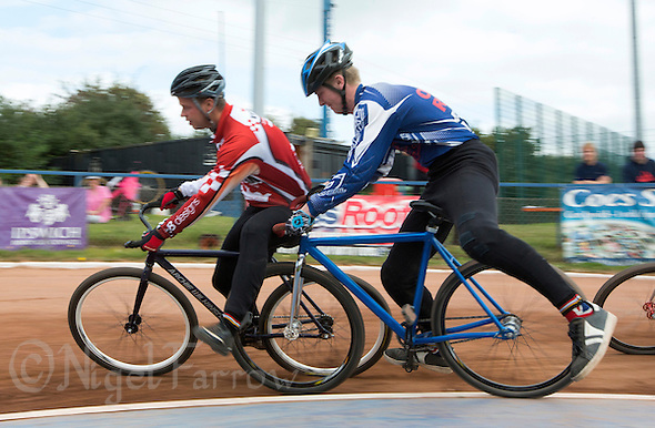 13 SEP 2014 - IPSWICH, GBR - Ollie Riley (right) from Hethersett Hawks gets his wheel trapped under the leg of  Marcus Wadhams from Birmingham Monarchs during a second semi final heat at the 2014 British Open Club Cycle Speedway Championships at Whitton Sports & Community Centre in Ipswich, Great Britain (PHOTO COPYRIGHT © 2014 NIGEL FARROW, ALL RIGHTS RESERVED) (NIGEL FARROW/COPYRIGHT © 2014 NIGEL FARROW : www.nigelfarrow.com)