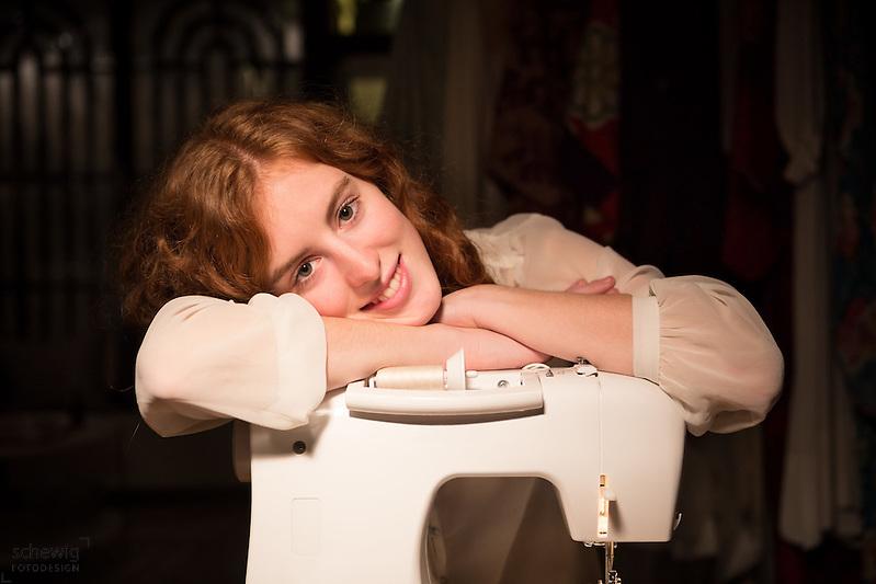 Junge Frau lehnt auf Nähmaschine in ihrem Workshop, Wien, Österreich, Jungunternehmerin im Kreativbereich, Portrait (Dieter Schewig)