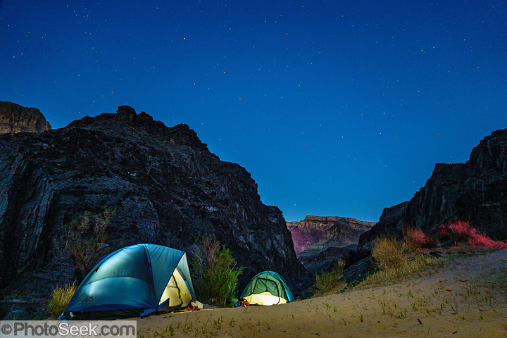 Tents glow at night under the stars in Schist Camp in the Inner Gorge of Grand Canyon at Colorado River Mile 96.5 (measured downstream from Lees Ferry). Day 6 of 16 days rafting 226 miles down the Colorado River in Grand Canyon National Park, Arizona, USA. (© Tom Dempsey / PhotoSeek.com)