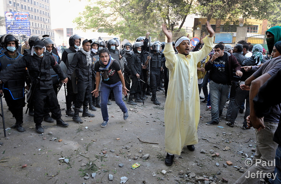 Two men urge their fellow demonstrators to move back from police in a confrontation during November 27, 2012, protests in Cairo's Tahrir Square. The protestors were upset by Egyptian President Mohammed Mursi's November 22nd decision to assume sweeping new powers.