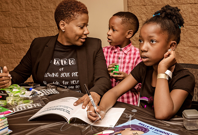 "Young author Nia Mya Reese, right, signs copies of her book, ""How to Deal with and Care for Your Annoying Little Brother,"" April 21, 2018, at Homewood Public Library in Birmingham, Ala. Her mother, Cherinita Ladd-Reese, left, helped her find a publisher for the book. Her brother, Ronald Michael Reese, center, served as the inspiration. Nia Mya, now 9 years old, was 7 when the book was published. (Photo by Carmen K. Sisson/Cloudybright) (Carmen K. Sisson/Cloudybright)"