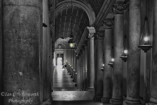 A view down a Vatican hallway in Rome in black and white with a hint of colour in the main light. (Ian C Whitworth)
