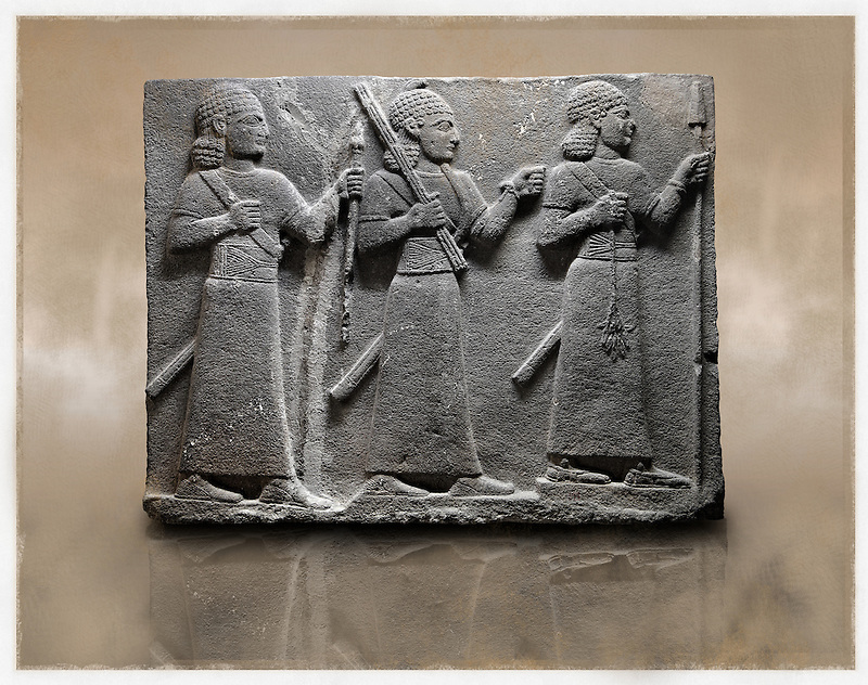 Picture & image of a Neo-Hittite orthostat of 3 warriors from the legend of Gilgamesh from Karkamis,, Turkey. Ancora Archaeological Museum. The warrior on the far left holds a spear in one hand and the branch of a tree in the other. The middle warrior has a clenched fist an carries an impliment over his shoulder. The warrior on the far right carries a saff. All 3 are wearing swords. 2 (Paul E Williams)