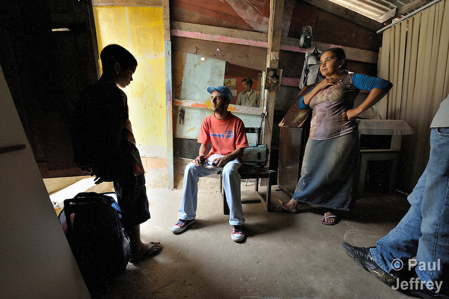 Rodrigo Mello, an outreach worker for the Street Children Project in Sao Bernardo do Campo, talks with 11-year old Gabriel Acevedo Silva in the doorway of the boy's home as his mother, Elismar do Nacimiento Acevedo, listens. The mirror on the wall shows another Project staff member, Leonardo Duarte.
