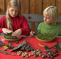 Kinder basteln Zwergengärtchen, Zwergen-Gärtchen aus Naturmaterialien, Bastelei, Tonschale wird mit Moos ausgelegt, Rinde, Eicheln, Kastanien, Äste und Blätter liegen zum Dekorieren bereit (Frank Hecker)