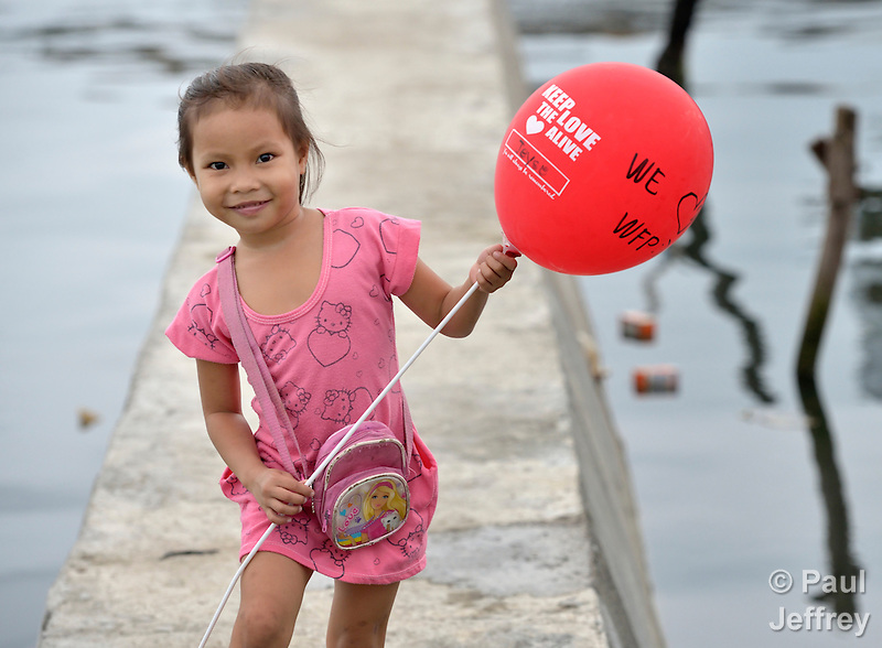 A girl walks with a balloon celebrating international solidarity with survivors in Tacloban, a city in the Philippines province of Leyte that was hit hard by Typhoon Haiyan in November 2013. The storm was known locally as Yolanda. The ACT Alliance has been active here and in affected communities throughout the region helping survivors to rebuild their homes and recover their livelihoods. (Paul Jeffrey)
