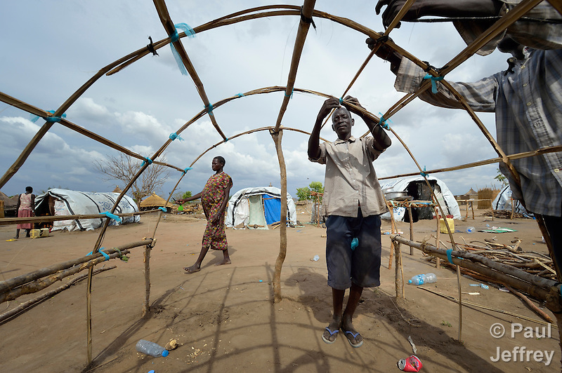 Gumbo Paul builds the framework for his family's tent in a camp for almost 500 internally displaced people located at the St. Vincent de Paul Catholic parish on the edge of Juba, the capital of South Sudan. The families here fled fighting that broke out in December 2013. Paul, along with his wife and five children, came to Juba from Bentieu. More than 700,000 people have been internally displaced in the first three months. (Paul Jeffrey)