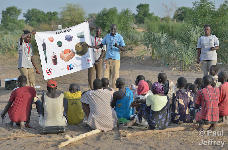 Members of an ACT Alliance team talk with villagers about the dangers of unexploded ordnance near the South Sudan town of Bor, which has been the scene of heavy fighting between government troops and rebels since a dispute within the ruling party turned violent in December 2013 and quickly ripped the newly independent nation along ethnic and tribal lines. The mine risk education team is part of the humanitarian mine action program of Dan Church Aid, a member of the ACT Alliance. The program also deploys explosive ordnance disposal teams to locate and safely remove dangerous items from this most recent conflict as well as ordnance left over from earlier decades of civil war. (Paul Jeffrey)