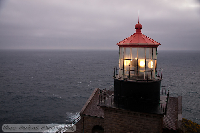 A view of the Pacific Ocean with Point Sur Light Station's light house in the foreground.  The sun has just set, and low marine clouds cover the sky, while the light can be seen rotating.  The view from the lighthouse is just stunning.  This view includes almost none of the hillside, as opposed to #2. (Marc C. Perkins)