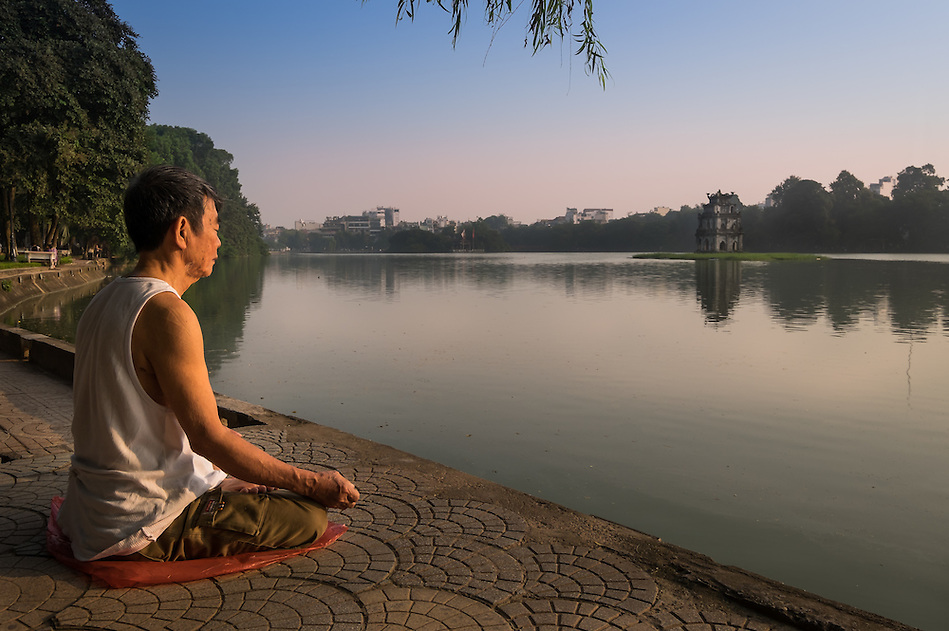 HANOI, VIETNAM - CIRCA SEPTEMBER 2014:  A Vietnamese man meditates early morning in the Hoan Kiem Lake, in Hanoi. (Daniel Korzeniewski)
