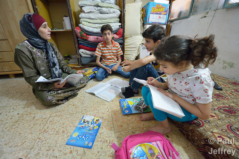 Ahlam Mazatha supervises the homework of her sons Mohammed, 13, and Abed Rahaman, 10, and her daughter Sarah, 5, in their small apartment in Madaba, a sprawling Palestinian refugee camp in Jordan that has grown in recent years with the arrival of refugees--like this family--from war-torn Syria. She and her husband and three children fled Daraa in 2013 when bombing destroyed their home. Mazatha was a teacher in Syria, and her husband owned a taxi, but in Jordan they are not allowed to work by the government. The Department of Service for Palestinian Refugees of the Middle East Council of Churches, a member of the ACT Alliance, provides a variety of services here, including medical care. (Paul Jeffrey)
