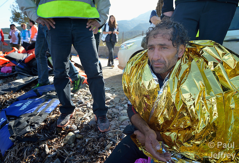 A suspected Turkish migrant smuggler sits on a beach near Molyvos, on the Greek island of Lesbos on October 31, 2015. He was rescued from the water after volunteers on the island punctured a raft in which he was trying to flee back to Turkey after depositing a load of refugees. He was turned over to the Greek police. (Paul Jeffrey)