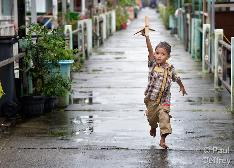 Five-year old Mohibuddin runs with his toy wooden airplane along a sidewalk in Kuala Bubon, in Indonesia's Aceh province. The community of 118 houses was built by the ACT Alliance after the village's tsunami survivors refused to accept government plans to relocate them inland far from the sea. After the houses were built, the community then successfully fought a government plan to demolish part of the new village to make way for a new highway. Parental consent obtained. (Paul Jeffrey)