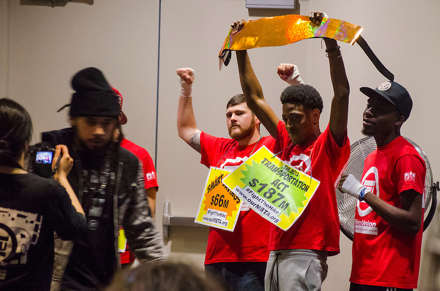 "2/2/16 – Boston, MA – Members of the T Riders Union enact a boxing match between ""Fare Hikes"" and alternatives in the conference room in the Massachusetts Department of Transportation building for a fare proposal hearing on Feb 2nd, 2016. (Ray Bernoff / The Tufts Daily) (Ray Bernoff)"