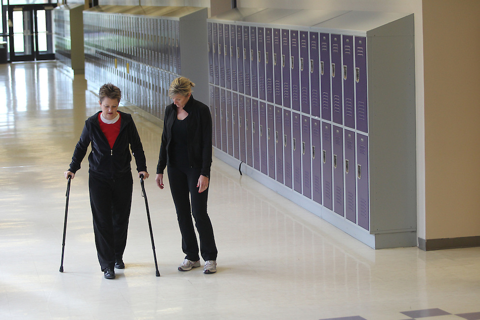 Gayla Tighe uses a pair of canes while walking with friend Glenda Criswell inside Indianola High School. Tighe walks the school's halls three times a week as part of her rehabilitation.  Last July, Gayla suffered a spinal cord injury and was paralyzed.  An accomplished pianist, Gayla has drawn on her faith and made great strides in her rehabiliatation.  Now, some eight months later, she is also beginning to play the piano again. (Christopher Gannon/The Register)