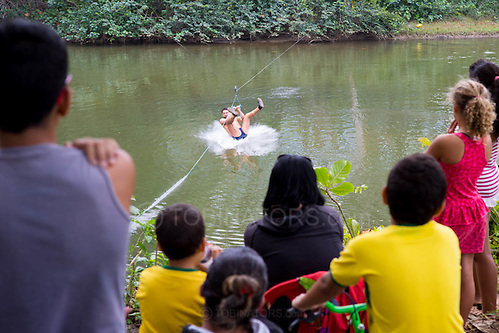 Villagers watch as a man has a go on the newly installed cable slide over the river at Dois Rios on the island of Ilha Grande, Brazil. Photo by Andrew Tobin/Tobinators Ltd (Andrew Tobin/Tobinators)