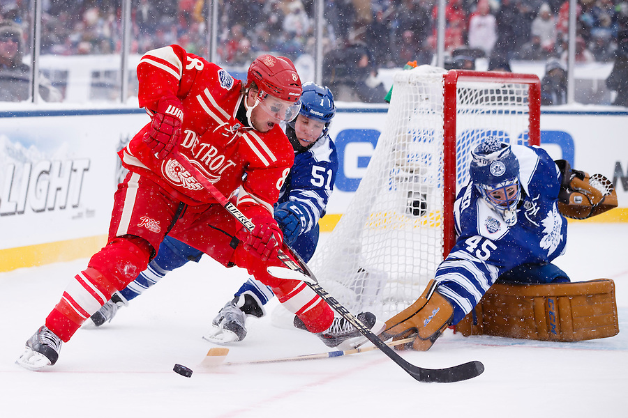 Jan 1, 2014; Ann Arbor, MI, USA; Toronto Maple Leafs goalie Jonathan Bernier (45) makes a save on Detroit Red Wings left wing Justin Abdelkader (8) as he is defended by Toronto defenseman Jake Gardiner (51) during the 2014 Winter Classic hockey game at Michigan Stadium. Mandatory Credit: Rick Osentoski-USA TODAY Sports (Rick Osentoski/Rick Osentoski-USA TODAY Sports)