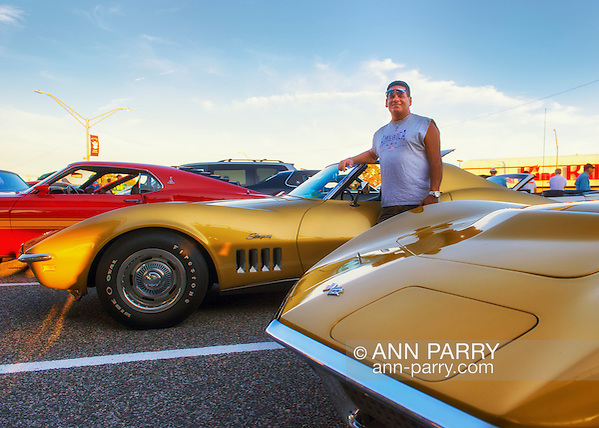 Bellmore, New York, USA. 7th August 2015. JIMMY STELLAS, of Freeport, is standing in front of his War Bonnet Yellow 1969 Corvette Stingray, at the Friday Night Car Show held at the Bellmore Long Island Railroad Station Parking Lot. Hundreds of classic, antique, and custom cars were on view at the free weekly show, sponsored by the Chamber of Commerce of the Bellmores. In front of Stellas is a Riverside Gold 1972 Stingray Vette. (Ann Parry/Ann Parry, ann-parry.com)