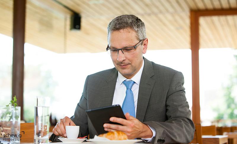 Österreich, Geschäftsmann mit Tablet Computer macht Kaffeepause in Restaurant (dieter schewig)