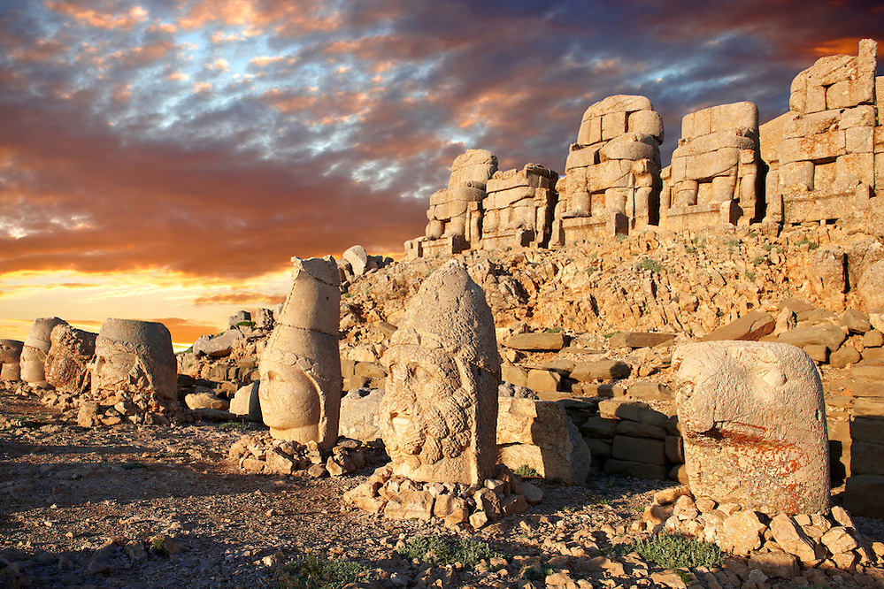 Pictures of the statues of around the tomb of Commagene King Antochus 1 on the top of Mount Nemrut, Turkey. Stock photos & Photo art prints. In 62 BC, King Antiochus I Theos of Commagene built on the mountain top a tomb-sanctuary flanked by huge statues (8–9 m/26–30 ft high) of himself, two lions, two eagles and various Greek, Armenian, and Iranian gods. The photos show the broken statues on the  2,134m (7,001ft)  mountain. 5 (Paul E Williams)