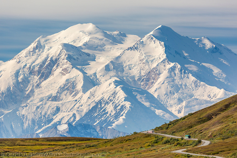 Tour bus travels the Denali Park Road through Thorofare Pass, with Denali visible along the Alaska Range horizon. (Patrick J. Endres / AlaskaPhotoGraphics.com)