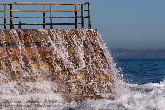 Water cascades over a brick sea wall at La Jolla Children's Pool, with its slightly rusty fence visible to the top.  A wave has just hit the wall, and white foamy water is flying over the bricks as the water crashes to the sea in front of the wall.  This contrasts with the perfectly calm blue water in the background. (Marc C. Perkins)