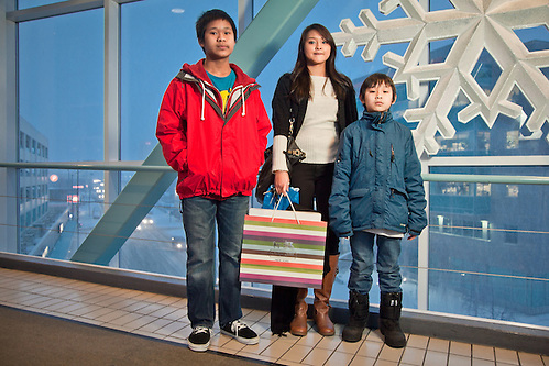 Christmas shoppers, Joseph, age 14, Kristi, age 17, and Austin, age 9, on the overpass at the Fifth Avenue Mall, Anchorage. (Clark James Mishler)