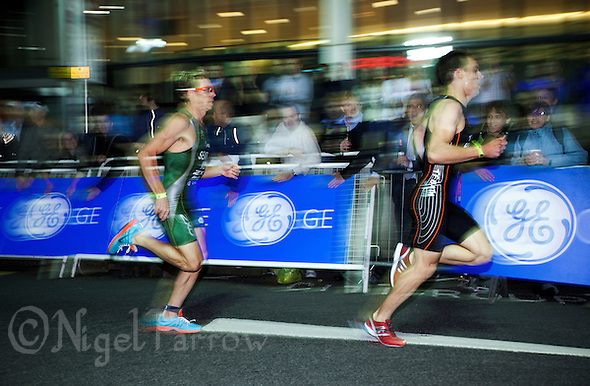 30 JUN 2011 - LONDON, GBR - Brett Sexton (left) and Aaron Harris make lead the field through the streets of Canary Wharf during the men's super sprint final at the GE Canary Wharf Triathlon .(PHOTO (C) NIGEL FARROW) (NIGEL FARROW/(C) 2011 NIGEL FARROW)