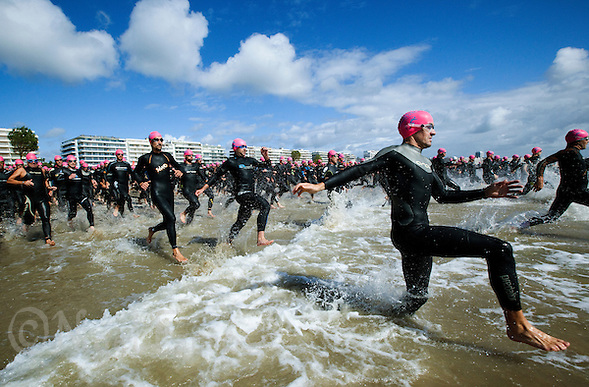 18 SEP 2011 - LA BAULE, FRA - Competitors run into the water at the start of the Triathlon Courte Distance (Olympic or standard distance) at the 24th Triathlon Audencia in La Baule, France .(PHOTO (C) NIGEL FARROW) (NIGEL FARROW/(C) 2011 NIGEL FARROW)