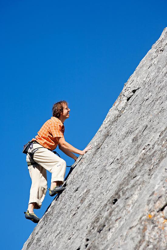 Male climber on rock face against blue sky, Banff, Banff National Park, Alberta, Canada (Brad Mitchell)
