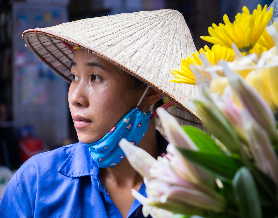 HANOI, VIETNAM - CIRCA SEPTEMBER 2014:  Portrait of Vietnamese woman selling flowers in the streets of Hanoi, Vietnam. (Daniel Korzeniewski)