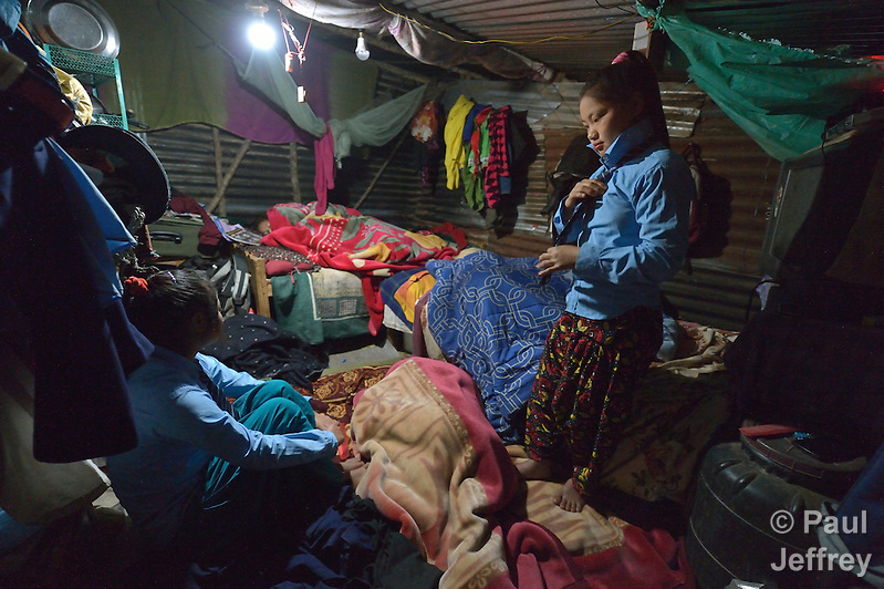 In the mountain village of Marpak, in Nepal's Dhading District, Preeta Tamang, 13, puts on her school uniform at 5:30 am, well before sunrise, as her sister Ritu, 14, looks on. The rest of their family remained asleep. The girls started class at 6 am. Their family's home was destroyed in Nepal's 2015 earthquake. (Paul Jeffrey)