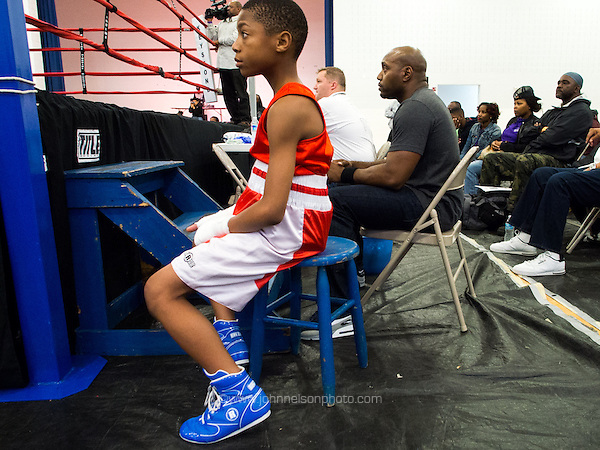 A young boxer watches a bout at ringside as he waits for his match at Calvin Woodland Sr Boxing tournament at the Merrick Recreation Center in Washington, DC. (John Nelson/photo by www.johnnelsonphoto.com)