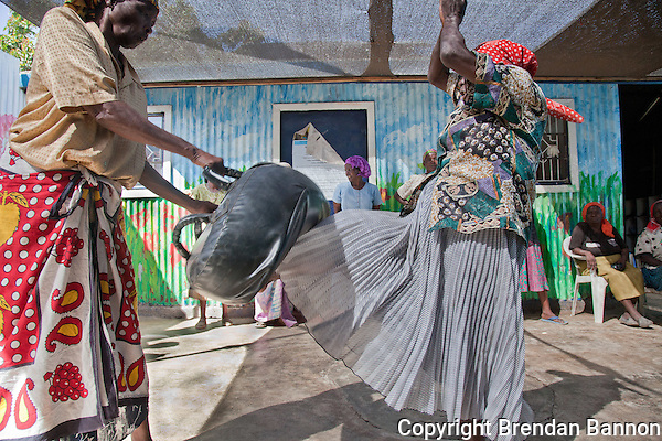 "Gender Defender coach Beatrice Nyariara (r), 68-years-old, demonstrates a self defence kick to the groin of her ""assailant."" She advised the self defence class for women ""make sure you don't miss the potatoes."" (Photographer: Brendan Bannon)"