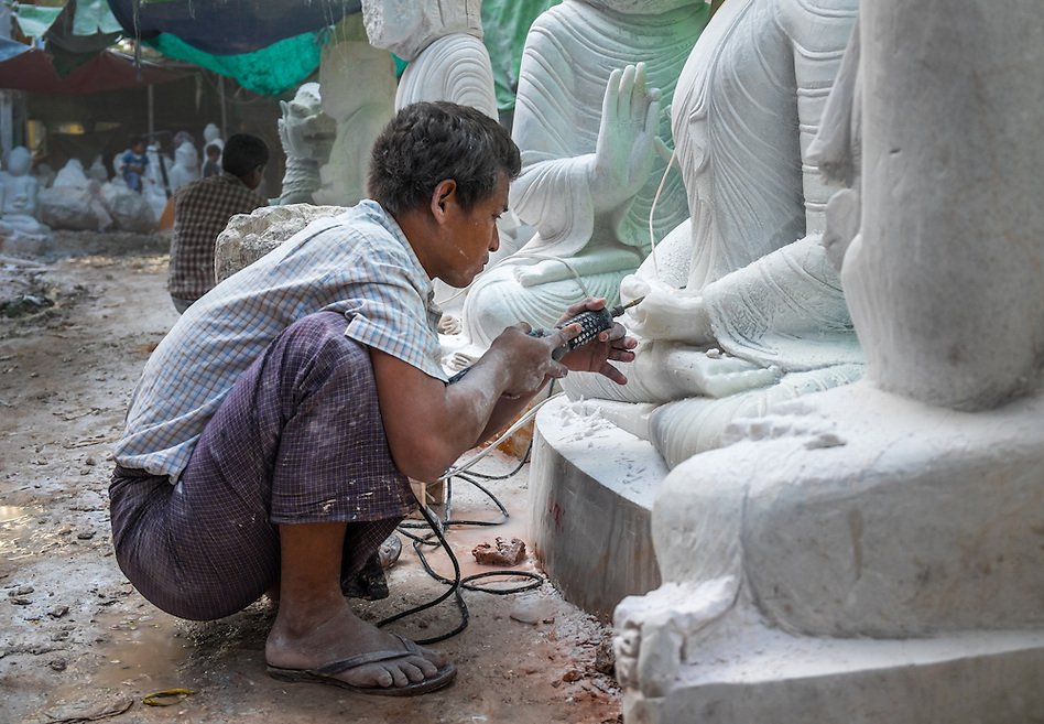 MANDALAY, MYANMAR - CIRCA DECEMBER 2013: Young man carving an image of Buddha marble in a workshop in Mandalay, Myanmar (Daniel Korzeniewski)
