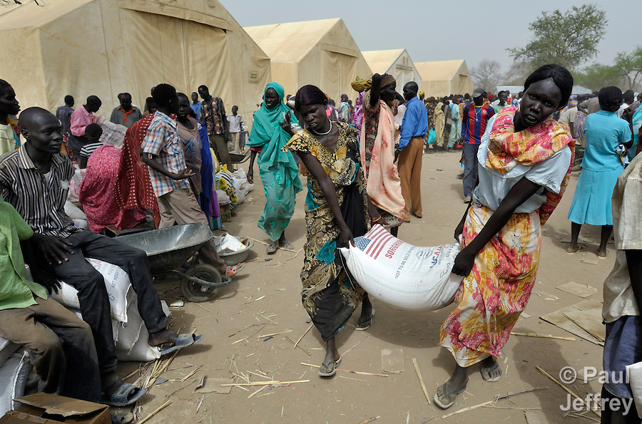 Women carry a bag of sorghum during a food distribution by the United Nations World Food Program in Agok, a town in the contested Abyei region where tens of thousands of people fled in 2011 after an attack by soldiers and militias from the northern Republic of Sudan on most parts of Abyei. Although the 2005 Comprehensive Peace Agreement called for residents of Abyei--which sits on the border between Sudan and South Sudan--to hold a referendum on whether they wanted to align with the north or the newly independent South Sudan, the government in Khartoum and northern-backed Misseriya nomads, excluded from voting as they only live part of the year in Abyei, blocked the vote and attacked the majority Dinka Ngok population. The African Union has proposed a new peace plan, including a referendum to be held in October 2013, but it has been rejected by the Misseriya and Khartoum. The Catholic parish of Abyei, with support from Caritas South Sudan and other international church partners, has maintained its pastoral presence among the displaced and assisted them with food, shelter, and other relief supplies. (Paul Jeffrey)