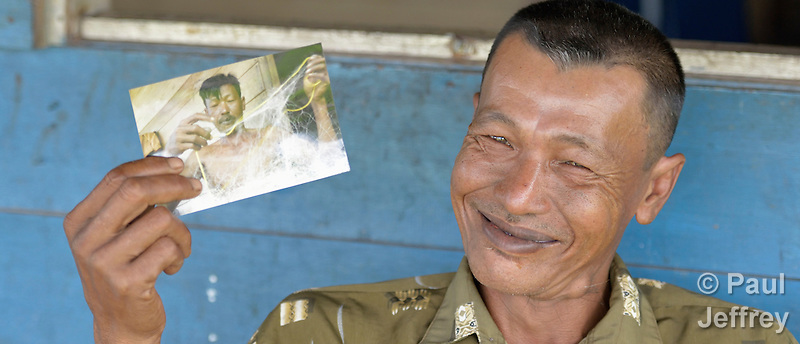 In 2014, Irman Baeha holds a photo of himself taken in 2007. He is a fisherman in the village of Moawo on the Indonesian island of Nias. His house was flattened by the 2004 tsunami, and he and his family later moved into a new house constructed by YEU, a member of the ACT Alliance. Yeu built 72 houses in the community. With foundations of cement, they are more resilient than the pre-tsunami houses which were built entirely of wood. YEU also helped the community members restart their local economy, and assisted the community as it planted mangroves to protect the shoreline and revitalize their fishing industry. Nias also suffered a devastating earthquake in 2005. (Paul Jeffrey)