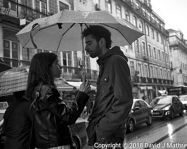 Rainy day discussion out on the street under an Umbrella in Lisbon. Image taken with a Leica CL camera and 23 mm f/2 lens. (David J Mathre)