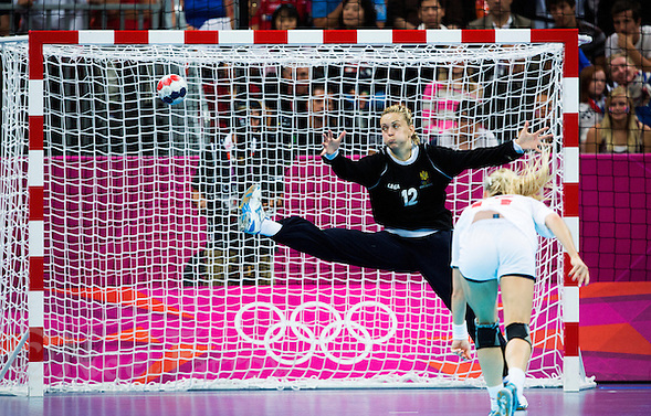 11 AUG 2012 - LONDON, GBR - Sonja Barjaktarovic (MNE) of Montenegro (left, in black) fails to save a shot from Linn Jørum Sulland (NOR) (right) of Norway during the women's London 2012 Olympic Games handball final at the Basketball Arena in the Olympic Park, in Stratford, London, Great Britain (PHOTO (C) 2012 NIGEL FARROW) (NIGEL FARROW/(C) 2012 NIGEL FARROW)