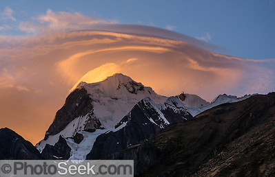 Golden sunrise light hits lenticular (lens-shaped, UFO-like) clouds capping Nevado Yerupaja Grande (6635 m or 21,770 ft), Peru's second highest peak. Seen from Incahuain / Jahuacocha campground on Day 9 of 9 days trekking around the Cordillera Huayhuash in the Andes Mountains, one day's walk from LLamac village, Peru, South America. (© Tom Dempsey / PhotoSeek.com)