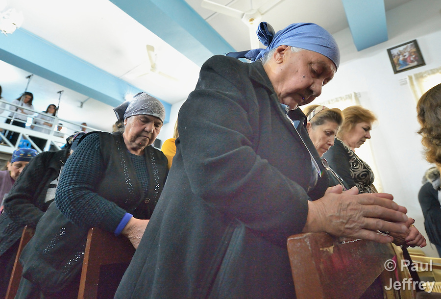 People pray during Mass in Inishke, Iraq, on April 10, 2016. Present was Cardinal Timothy Dolan, the archbishop of New York and chair of the Catholic Near East Welfare Association. He came to Iraqi Kurdistan with other church leaders to visit with Christians and others displaced by ISIS. Along with other church leaders, he celebrated Mass in the Chaldean Catholic church with local residents and displaced Christians living in local villages. CNEWA is a papal agency providing humanitarian and pastoral support to the church and people in the region. (Paul Jeffrey)