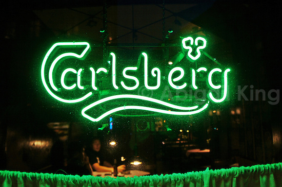 Illuminated green Carlsberg sign in the window of a pub or bar in Copenhagen, Denmark. (Abigail King)