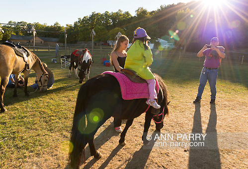 Old Bethpage, New York, U.S. 29th September 2013. A father takes a photo of his daughter riding a pony as closing time arrives at The Long Island Fair. A yearly event since 1842, the county fair is now held at a reconstructed fairground at Old Bethpage Village Restoration. (Ann Parry/Ann Parry, ann-parry.com)