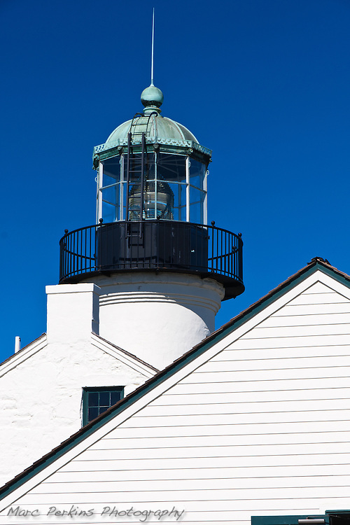 Old Point Loma Light is in Cabrillo National Monument near San Diego, CA.  This image is made from just south of the assistant keeper's house, showing the points of both the roofs of that building and the main lighthouse with its chimney.  Behind these, standing tall, is the lantern room of the lighthouse, with its installed lens.  The bright white buildings contrast with the clear blue sky and black lantern room. (Marc C. Perkins)
